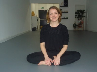 Beccy Watkinson, owner of Bind Yoga, sitting in yoga pose