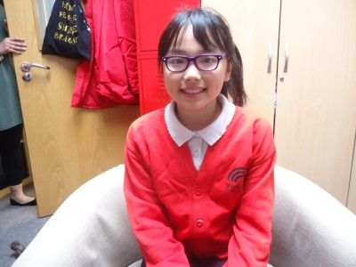 Jiaqi, Mayor for the Day, sitting in a chair