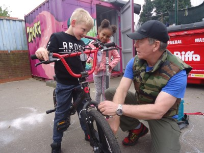 Tam Carrigan teaching two children about bikes